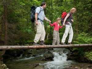 Family crossing a log over a stream